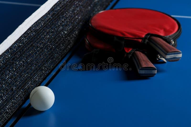 球蓝色桨乒乓切换技术天空乒乓球 台球球拍和球的辅助部件在一张蓝色网球桌上 体育运动 比赛体育运动 免版税库存图片