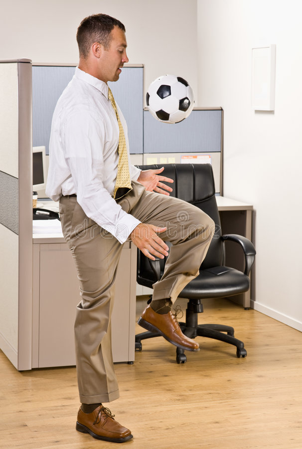 球踢足球的生意人办公室 免版税库存照片