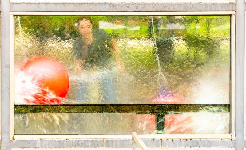 球通过与水枪的一个篮子被冲洗儿童` s比赛的抽象图片,从玻璃的后面射击 库存照片