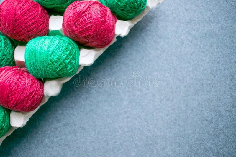 球颜色在纸蛋盘子的红色和绿色毛线 Diagona 库存图片