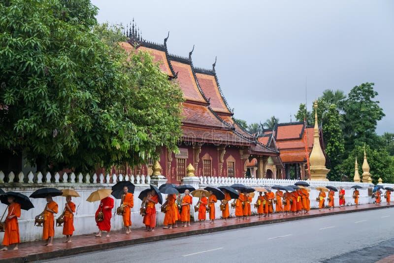 琅勃拉邦,老挝-大约2015年8月:分布的食物传统救济仪式对和尚的在街道上  免版税库存图片