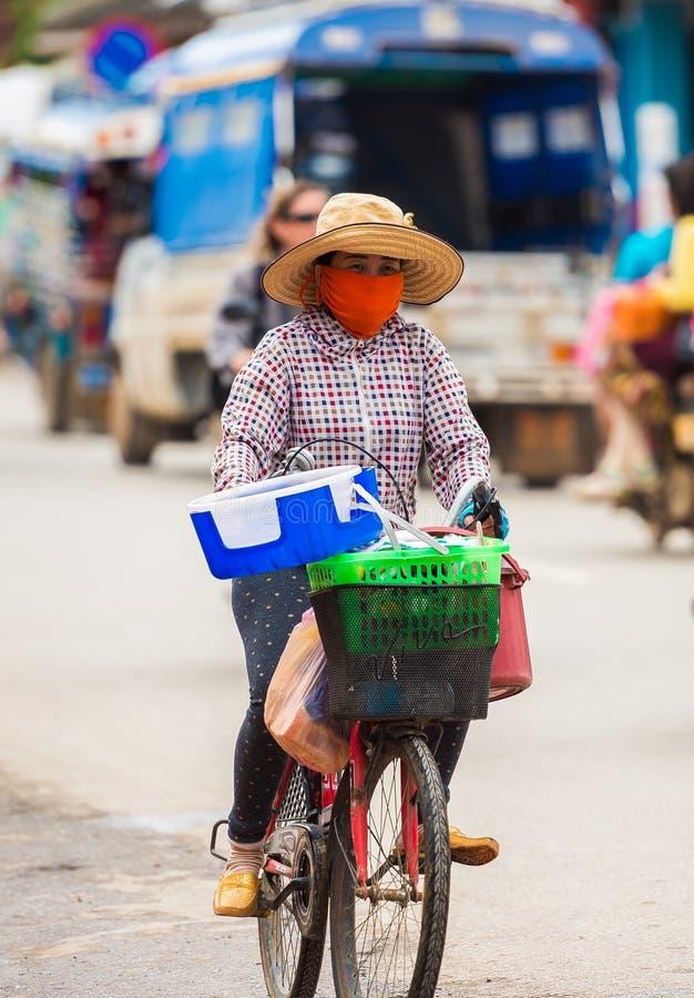 琅勃拉邦,老挝- 2017年1月11日:在城市街道上的骑自行车者 复制文本的空间 垂直 图库摄影