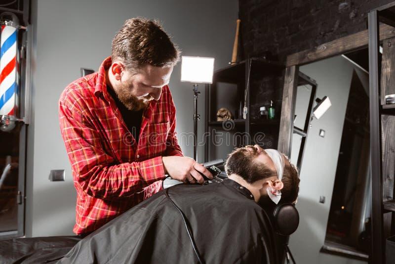 理发师与飞剪机机器一起使用在理发店 专业整理者工具剪年轻人的胡子和头发理发师的 免版税库存图片