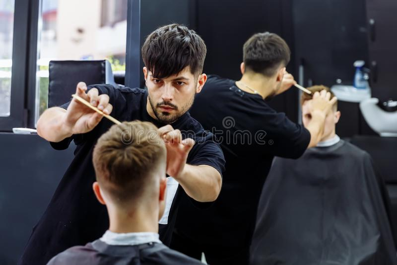 理发师做称呼与发胶和梳子的头发在理发以后在理发店 年轻英俊白种人人得到 库存图片