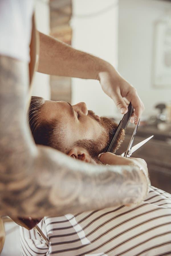 理发师切开与剪刀和梳子的客户` s胡子 免版税库存照片
