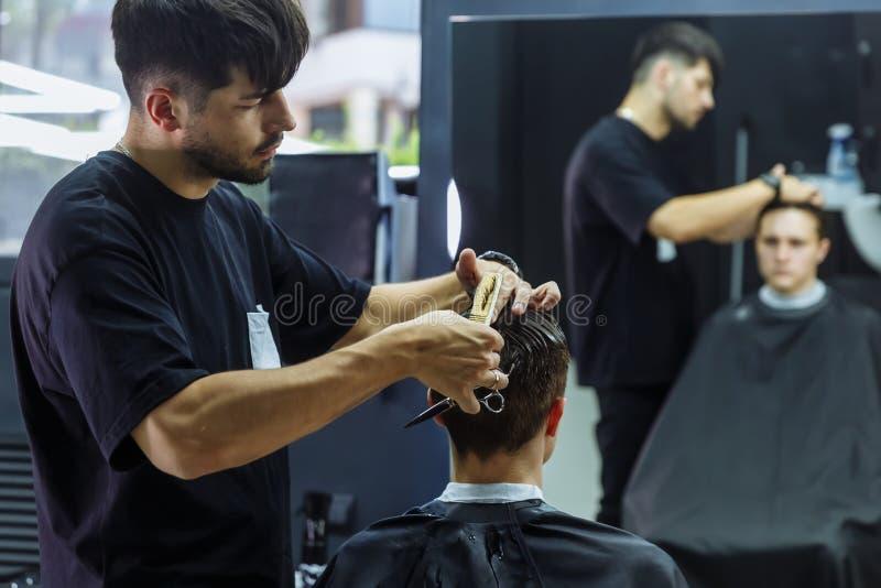理发师剪客户的头发有剪刀的 ?? 可爱的男性得到在理发店的现代理发 免版税库存图片