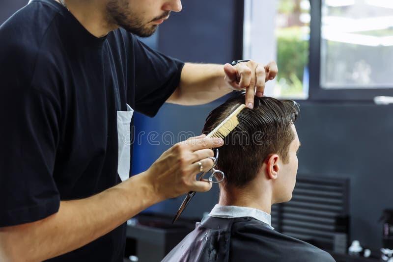 理发师剪客户的头发有剪刀的 ?? 可爱的男性得到在理发店的现代理发 免版税库存照片