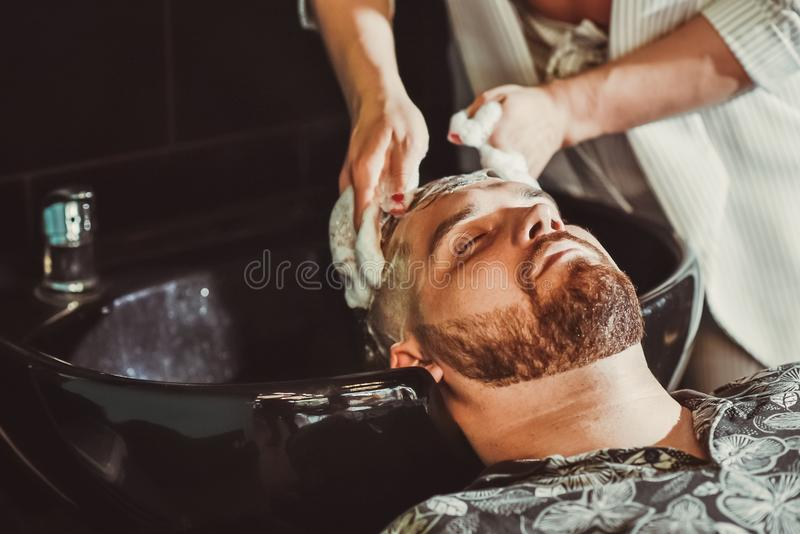 理发师在理发前洗一个有胡子的人的头发 免版税库存图片