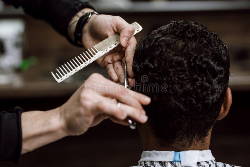 理发师在理发店剪拿着剪刀的一个人的头发并且梳在他的在镜子对面的手上 免版税图库摄影