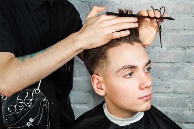 理发师头发称呼年轻人在砖墙背景的,美发师理发店做年轻人的发型 免版税库存照片