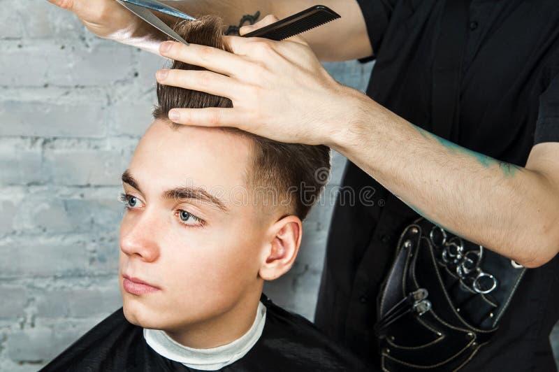 理发师头发称呼年轻人在砖墙背景的,美发师理发店做年轻人的发型 免版税库存图片