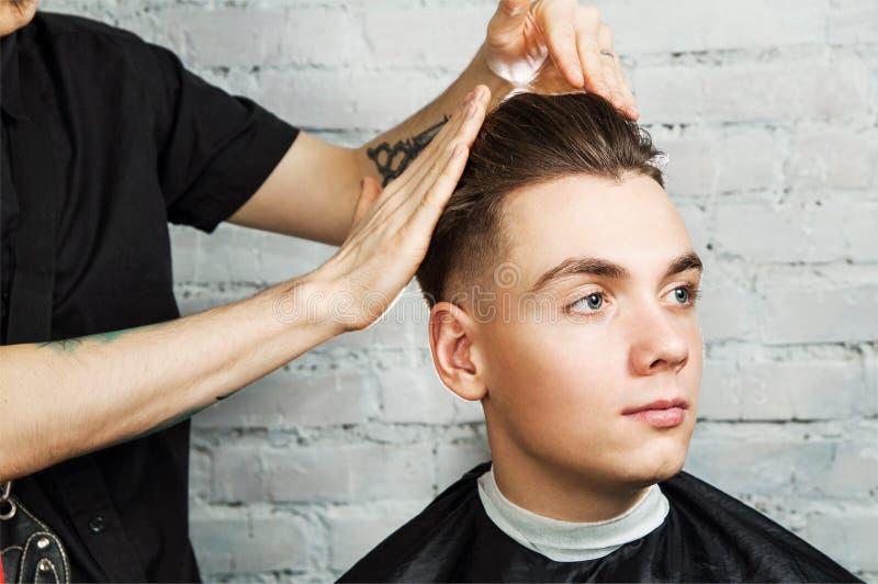 理发师头发称呼年轻人在砖墙背景的,美发师理发店做年轻人的发型 免版税图库摄影