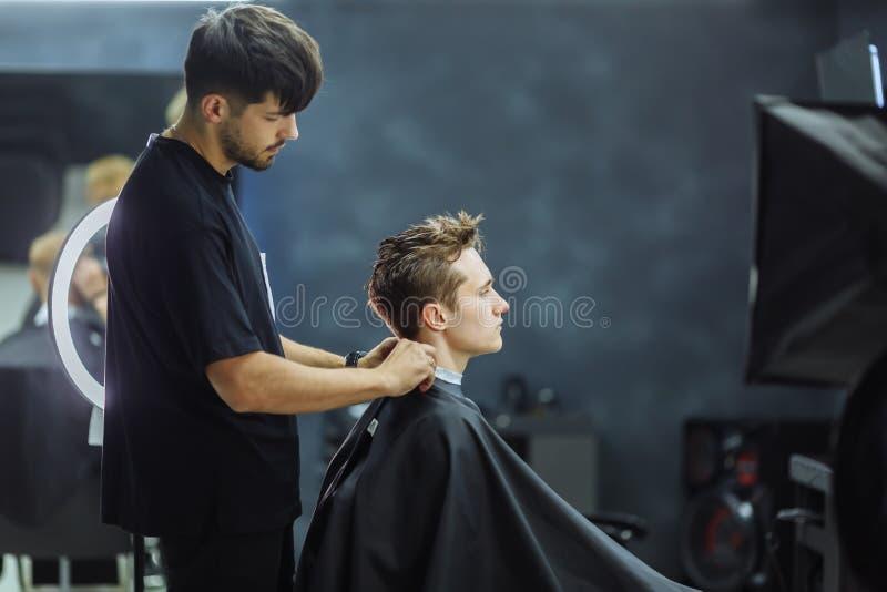理发师客户为新的发型理发店做准备 穿黑褂子的人坐在椅子和看镜子 免版税库存照片