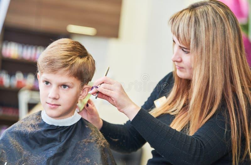 儿童理发 理发师或美发师在工作 美发师男孩客户的切口头发有剪刀的图片