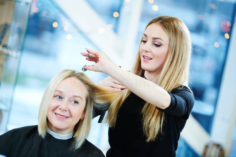 理发师或美发师在工作 美发师切口妇女头发 免版税库存照片