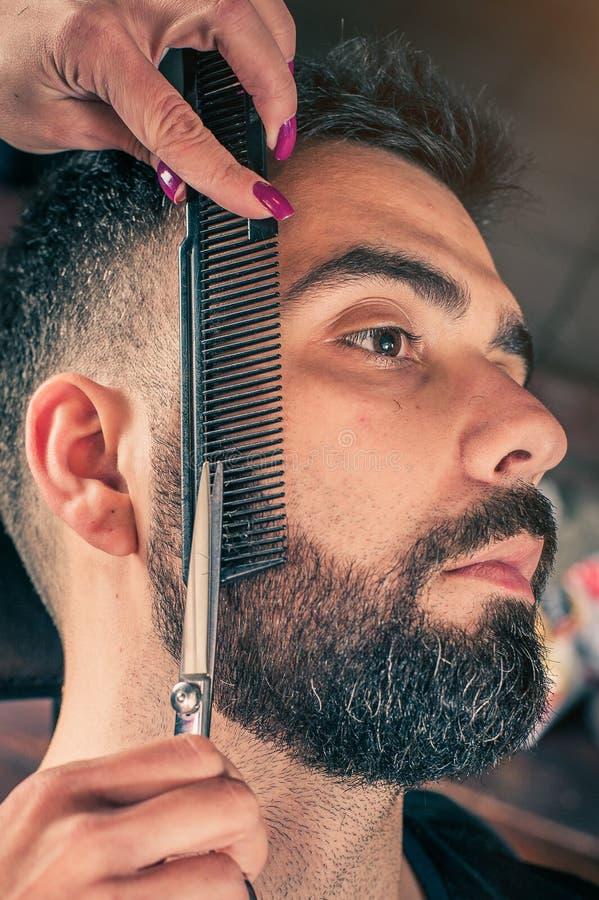 女性理发师胡子切开了与飞剪机的客户的胡子在理发店 特写镜头