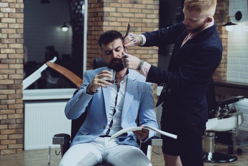 理发店内部的专业发式专家 得到理发的男性客户由美发师 在干燥身体局部的香脂 免版税库存图片