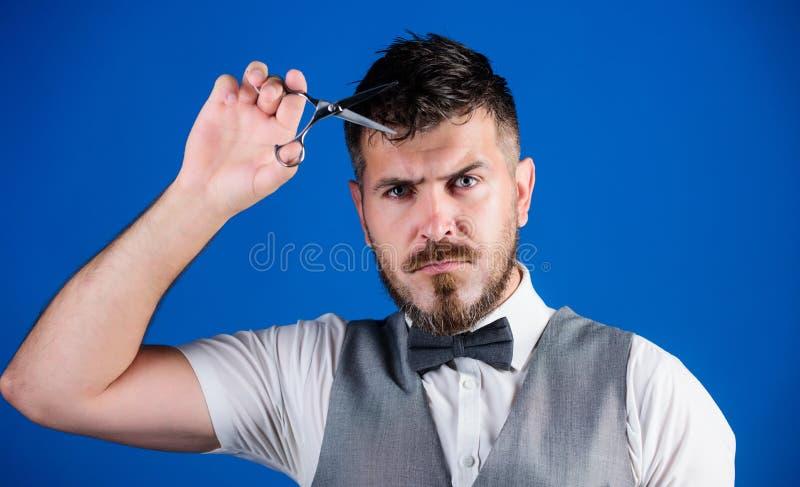 理发店服务概念 商人严密的面孔举行剪刀 有胡子和髭举行钢剪刀的理发师 库存照片