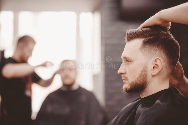 理发店横幅 理发椅的人,称呼他的头发的美发师 库存照片