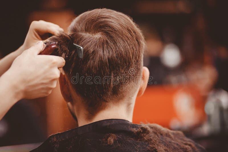 理发店横幅 理发椅的人,称呼他的头发的美发师 图库摄影