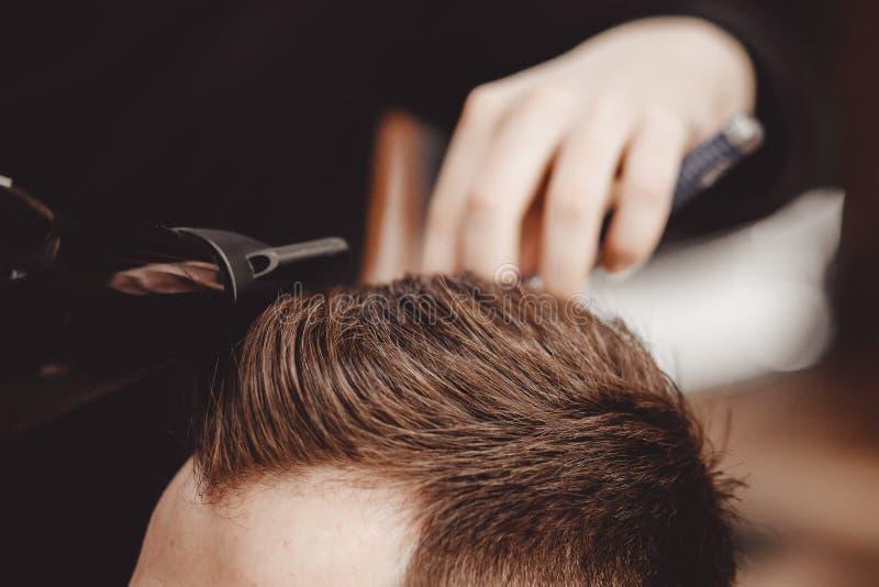 理发店,人美发师的人理发师做有剪刀的头发 免版税库存图片