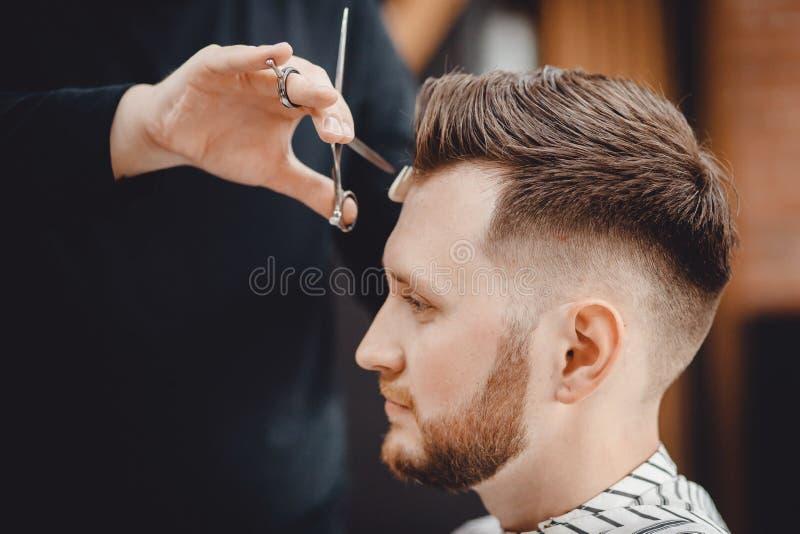 理发店,人美发师的人理发师做有剪刀的头发 免版税库存照片
