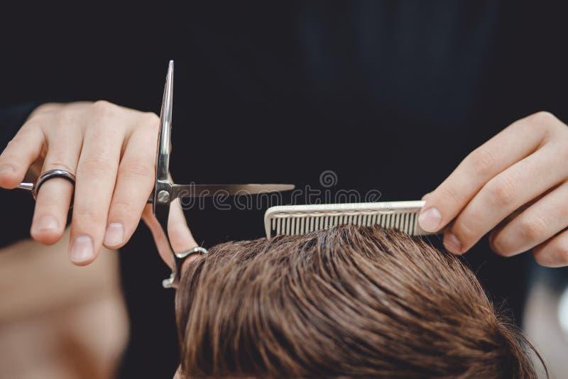 理发店,人美发师的人理发师做有剪刀的头发 免版税图库摄影