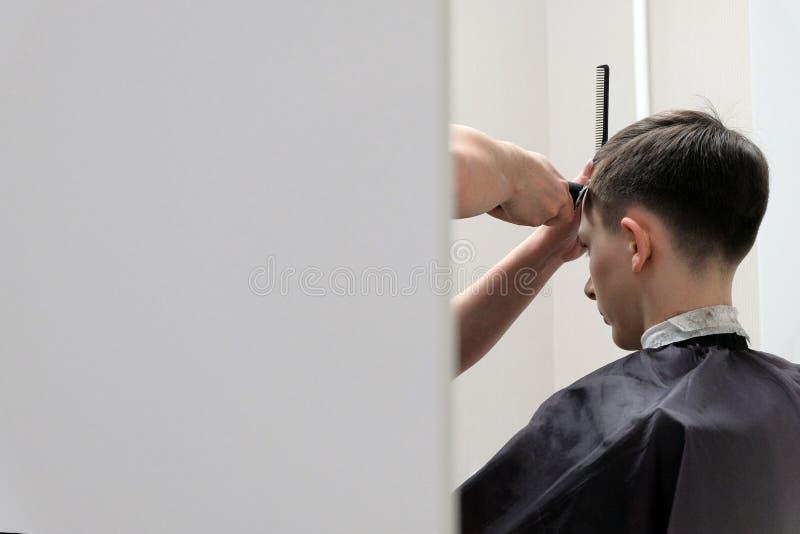 理发的年轻人在理发店 从在附近的照相 r o a的少年 免版税库存图片