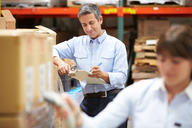 经理在有工作者扫描箱子的仓库里在前景 免版税库存照片