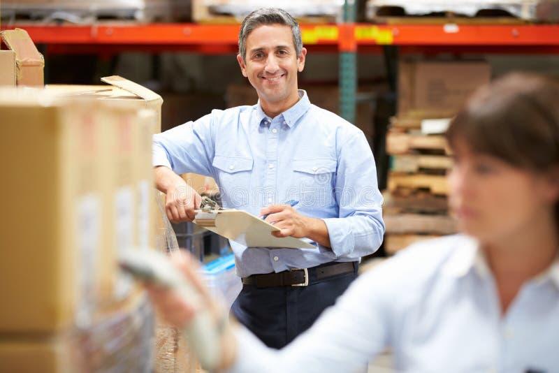 经理在有工作者扫描箱子的仓库里在前景 库存照片