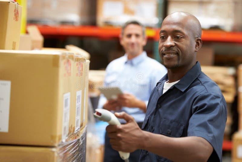 经理在有工作者扫描箱子的仓库里在前景 免版税图库摄影