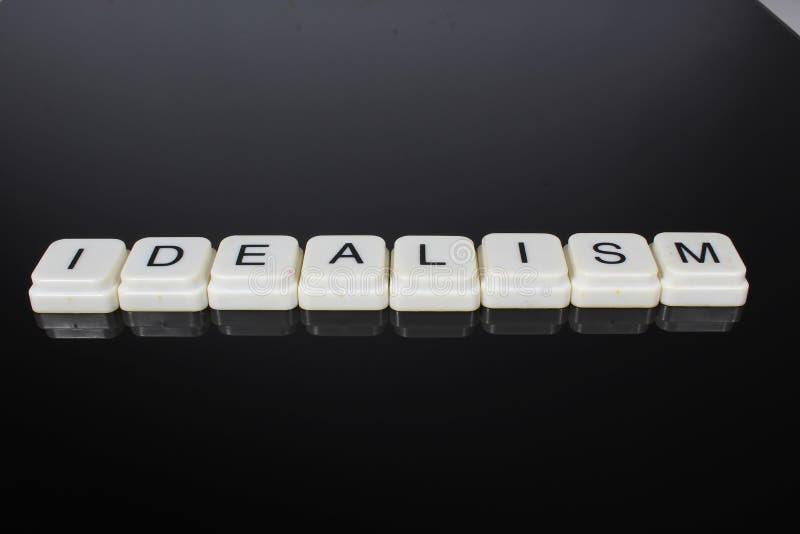 理想主义文本词标题说明标签盖子背景背景 字母表信件在黑反射性背景的玩具块 空白 免版税图库摄影