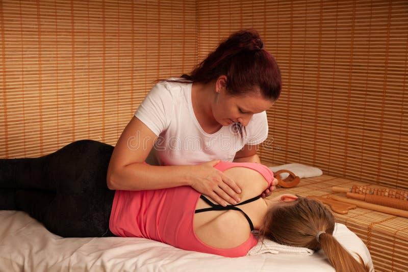 理疗的疗法-工作在患者的治疗师回到增量m 图库摄影