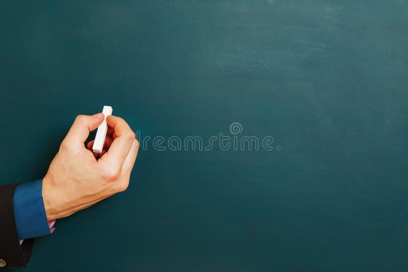 经理的手有白垩的在黑板 库存照片