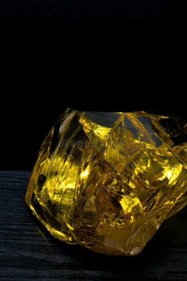 琥珀美好的大片断在黑背景的 太阳石头 石化树脂是首饰的自然水晶材料 葡萄酒 库存图片