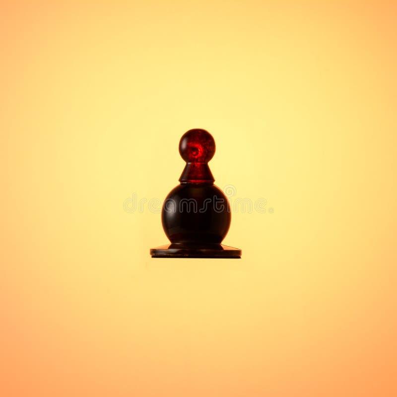 琥珀色的国际象棋棋局 棋子在金子梯度背景的黑色典当 库存图片
