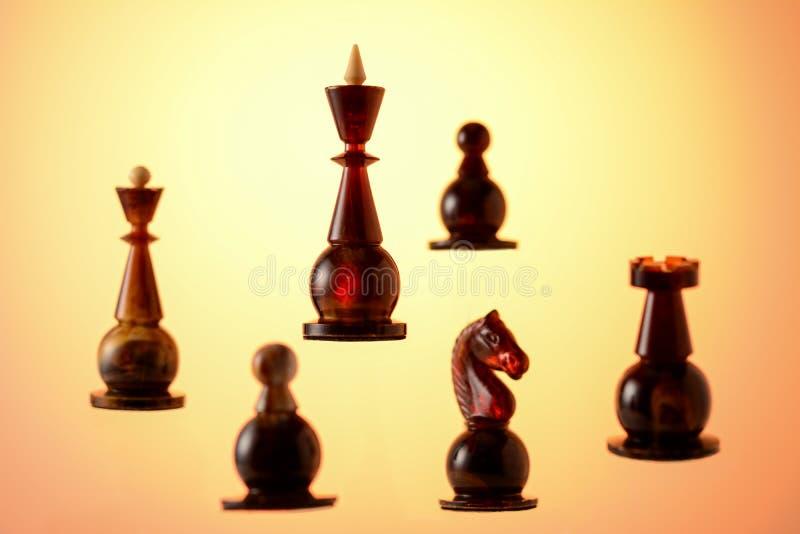 琥珀色的棋 棋子黑色国王由他的盟友围拢 图库摄影