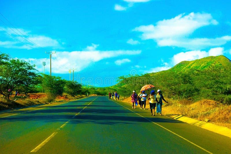 琥珀色的过滤器-佛得角人,走沿着路,普腊亚郊外,非洲风景 免版税库存图片