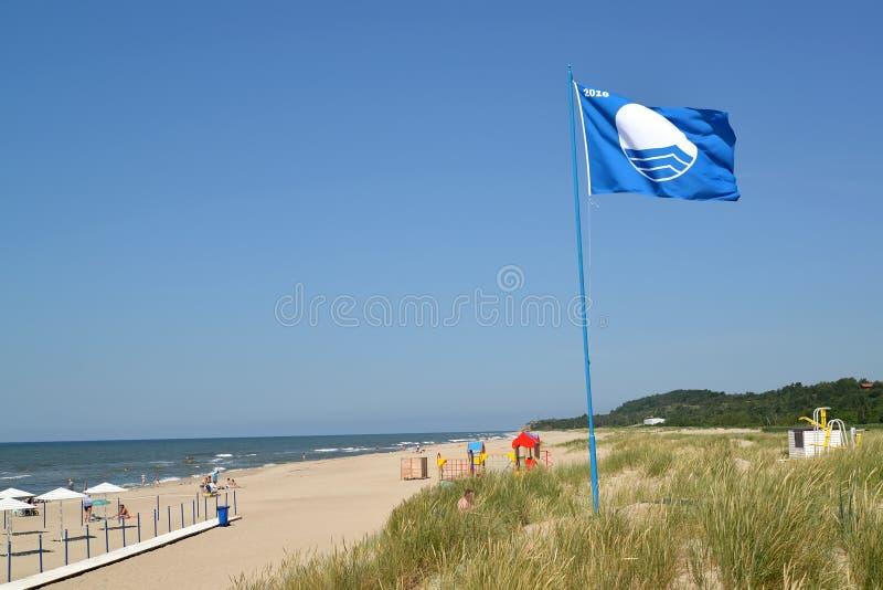 琥珀,俄罗斯 海滩蓝旗信号的国际标志振翼在城市海滩,加里宁格勒地区 库存图片
