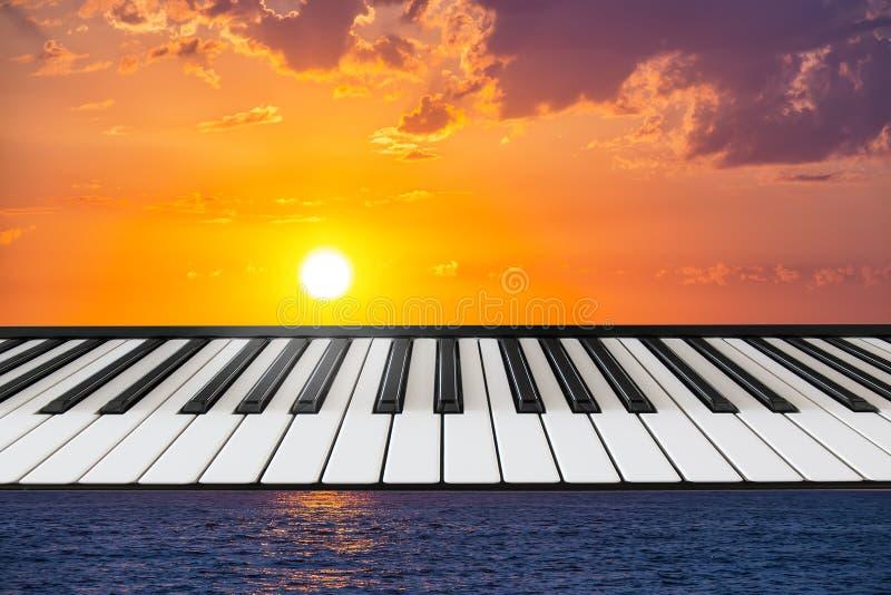 琴键的构成在海洋背景的与落日 免版税库存照片