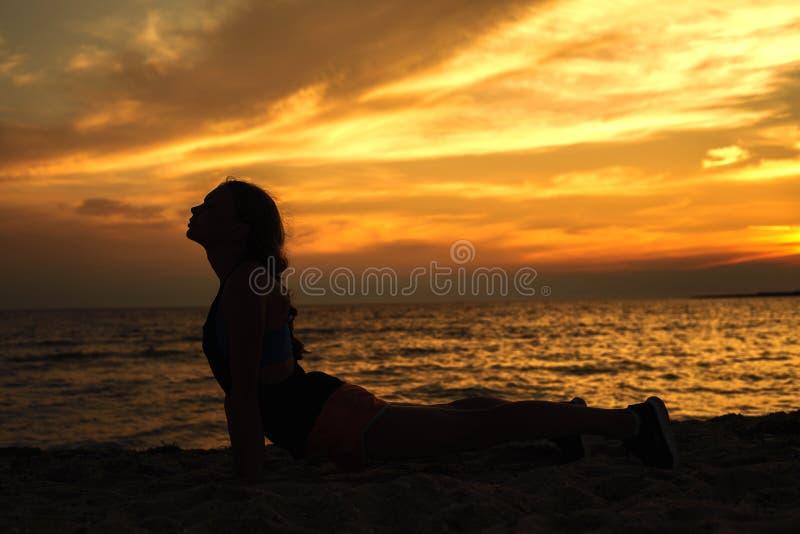 瑜伽做在海海滩的妇女剪影锻炼在su期间 免版税库存图片