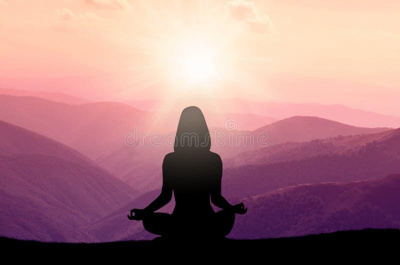 瑜伽和凝思 妇女剪影山的 库存图片