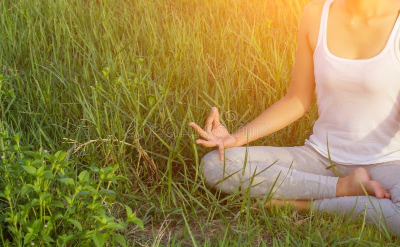 瑜伽在城市:美丽的年轻适合的思考妇女佩带的运动服,呼吸,坐与在半莲花的盘的腿 库存图片