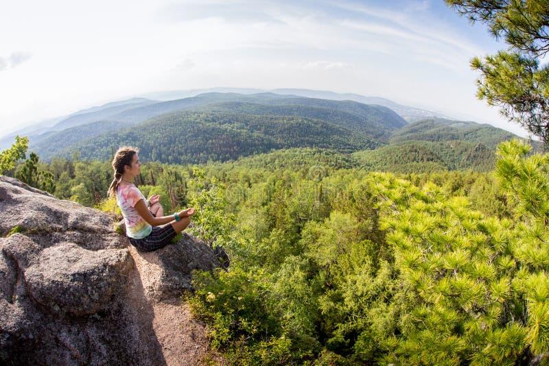 年轻瑜伽妇女凝思坐山峰 库存照片