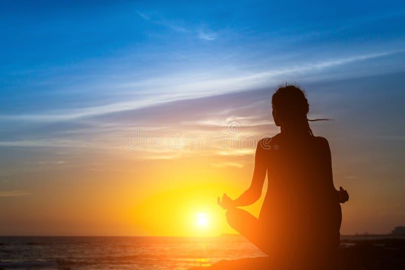 瑜伽妇女在海海滩的剪影凝思图片