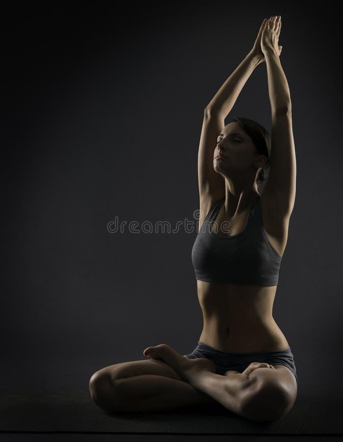 瑜伽妇女思考坐在莲花姿势 Silhoue 免版税库存照片