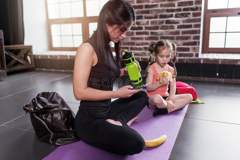 瑜伽孩子辅导员和女孩有断裂在锻炼以后坐席子饮用快餐,饮用水,使用电话 图库摄影
