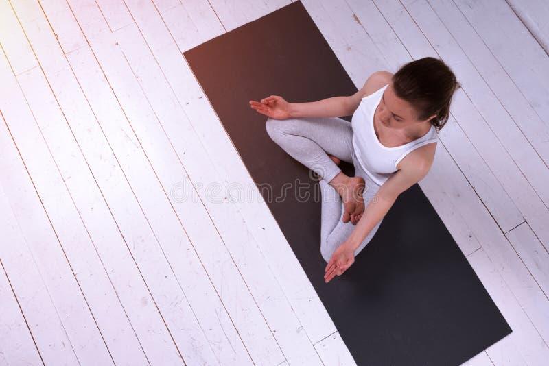 瑜伽室内凝思姿势的轻松的少妇 免版税图库摄影
