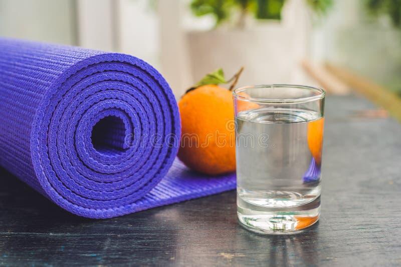 瑜伽席子、水、桔子和芒果在木背景 瑜伽的设备 概念健康生活方式、饮食和体育 复制Spac 免版税库存图片