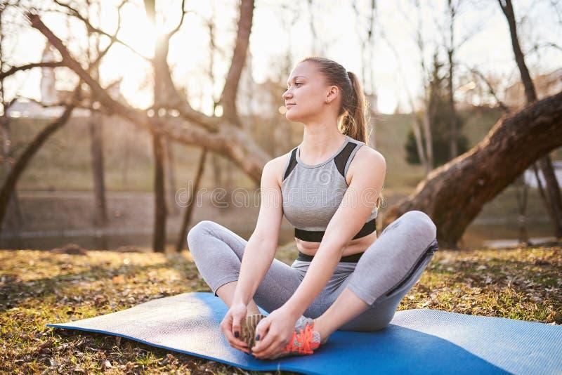 瑜伽席子的女孩在公园 免版税库存照片